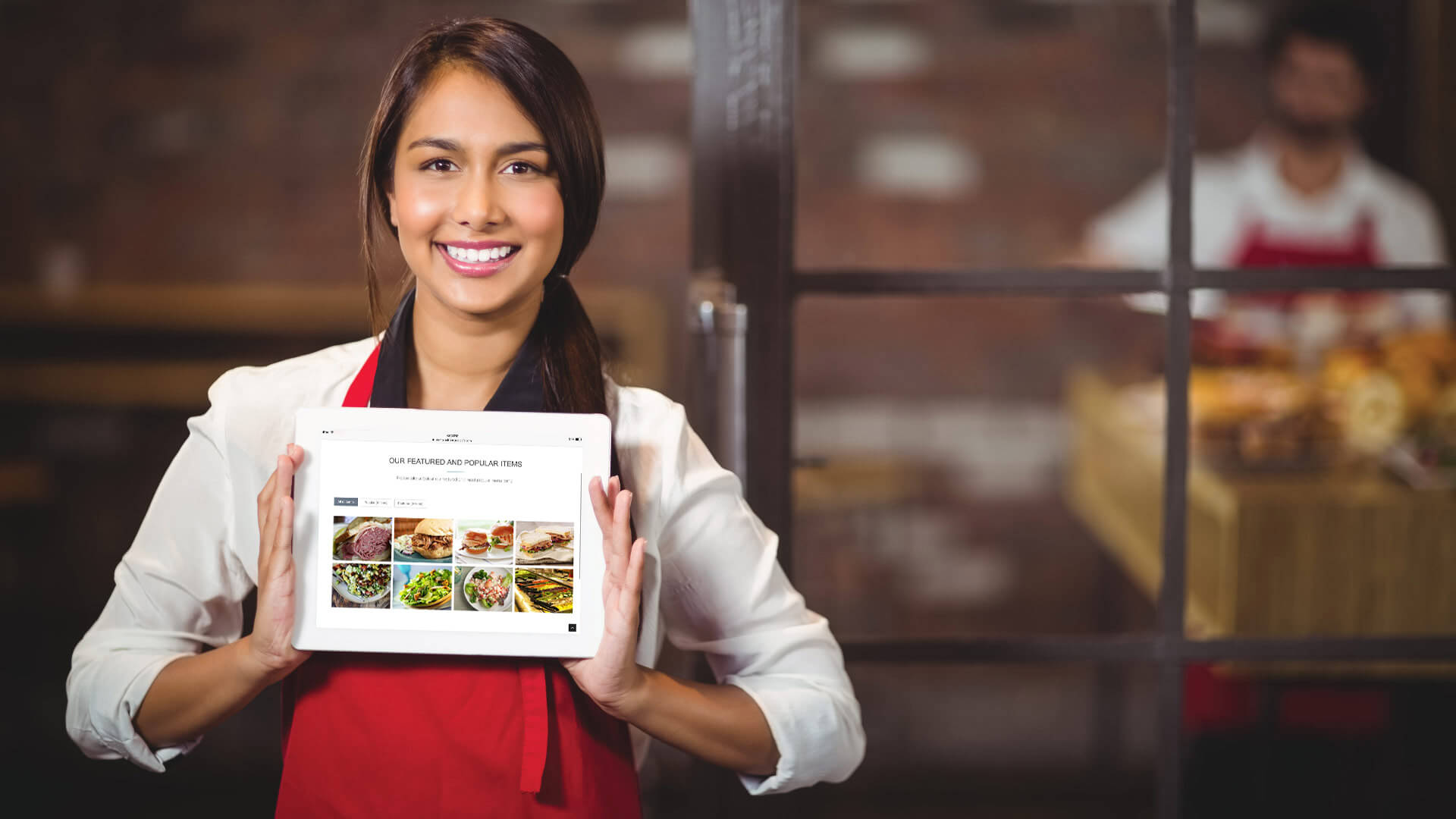 Smiling waitress holding a tablet with their restaurant's website on it - powered by Daily Delivery.
